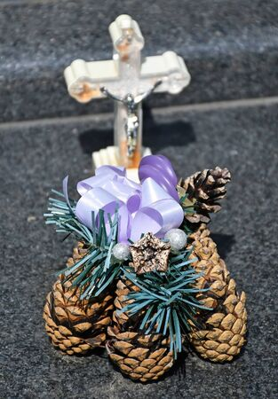 Cross and pine cones on the tombstone