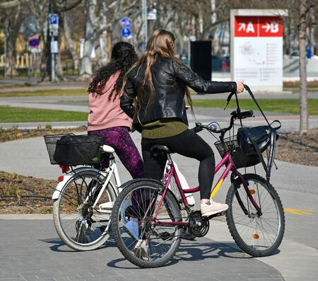 Young women with bicycles on the city street Stock Photo