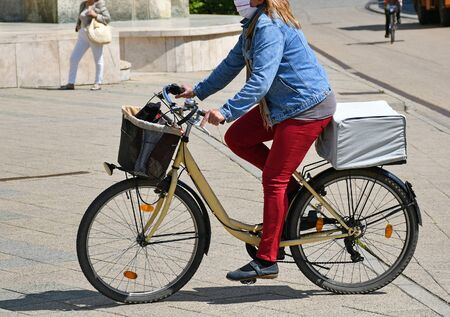 Woman rides a bicycle in a protective mask