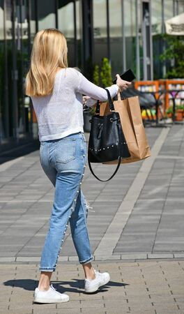 Young woman with shopping bag and smartphone in hand