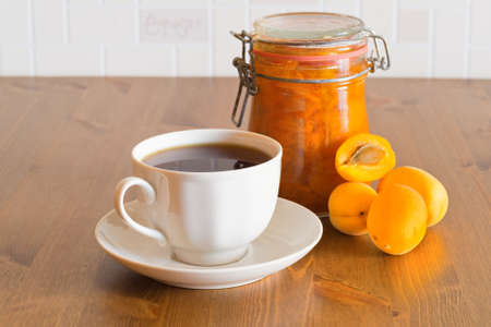 Homemade organic apricot jam in glass jar with apricots and tea on wooden table Stock Photo