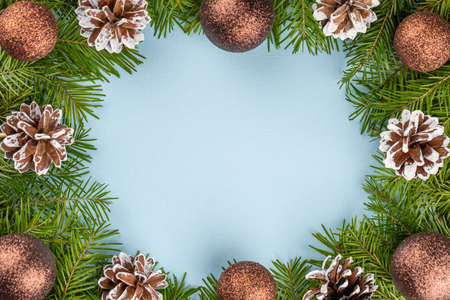 Beautiful Christmas decorations and green conifer branches on a blue background with free space for text. Flat lay. Greeting card merry Christmas, happy New year.