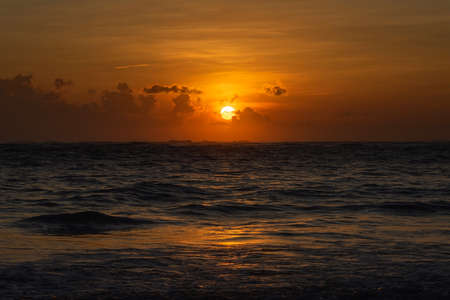 Sunrise over the ocean. The sun rises above the horizon through the clouds and paints the sky a Golden color.