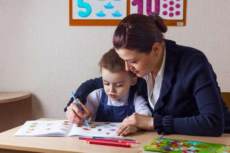 teaches: teacher teaches a young child at a school desk