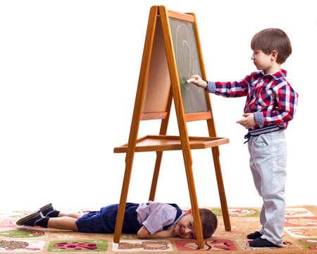 schooltime: children draw children draw with chalk on a blackboard white background
