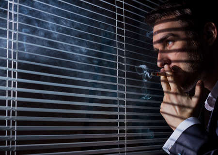 window blinds: business man smokes at the window blinds