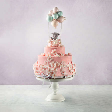 Tiered cake for birthday. Beautiful festive rose cake decorated with toy bear and baloons, white flowers over gray concrete background.