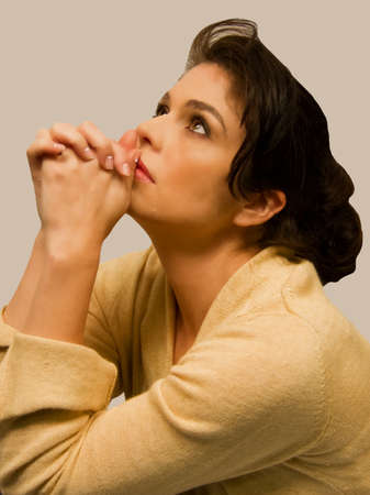 clasped hand: Female rests chin on clasped hands as she looks upward. Stock Photo
