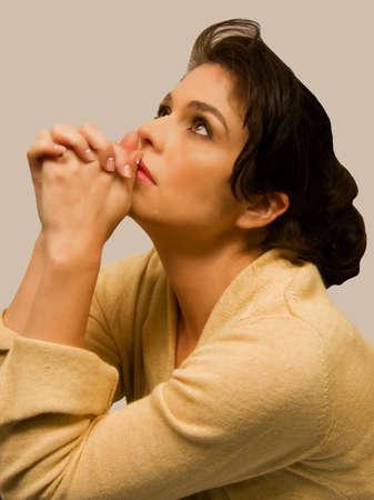 mujeres orando: Hembra descansa barbilla en manos apretadas como ella mira hacia arriba. Foto de archivo