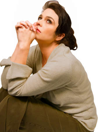 questioning: Emotional woman sitting with hands clasped looking upward. Stock Photo
