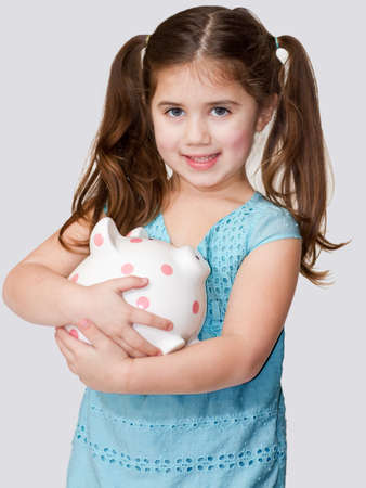 Cute little girl cradles a polka dotted piggybank in her arms.