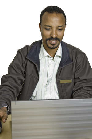 Young happy, smiling and diverse man sits at desk using laptop photo