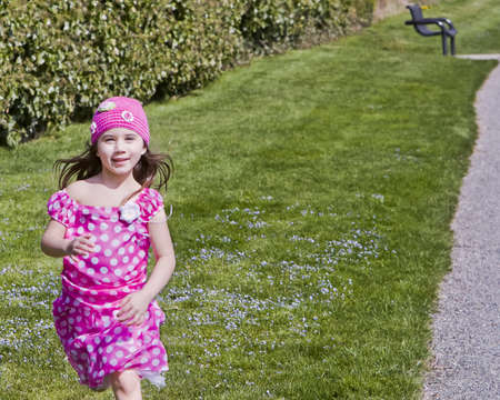 Young carefree girl running in park photo