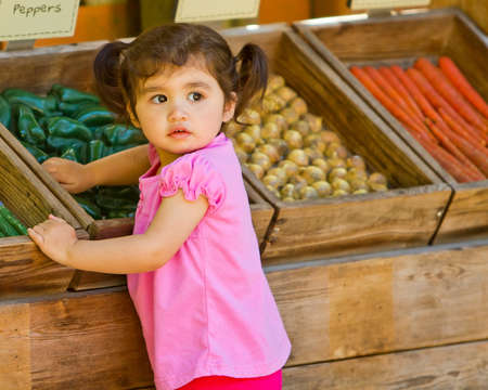 Young girl plays with veggies
