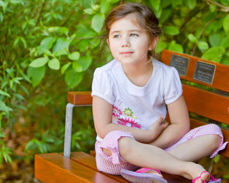 Young girl on thinking on bench