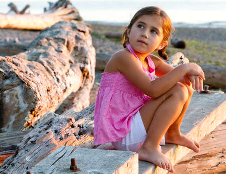 Beautiful girl sitting on log stares at the sky photo