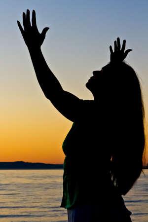 Woman raises arms to sky