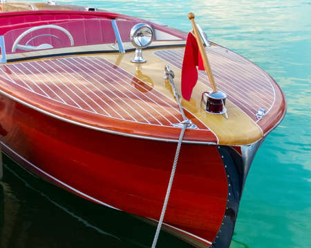 Two-toned classic wooden boat docked at side slip Archivio Fotografico