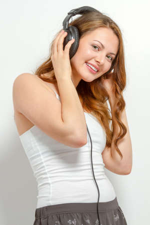 Cute happy young woman listens to headphones Stock Photo