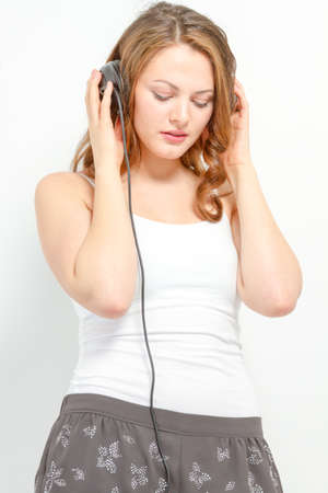 coed: Girl leisurely listens to audio Stock Photo