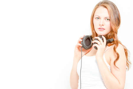 Goregous young woman holds headphones around neck