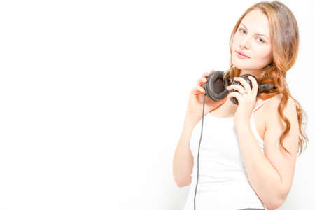 Goregous young woman holds headphones around neck photo