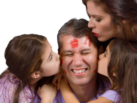 Mother and daughters leave lipstick kisses on dads face photo