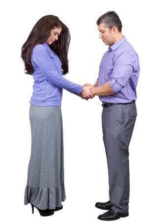 Husband and wife hold hands and pray as believers Stock Photo