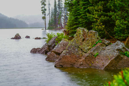 protrude: Ancient lava flow boulders protrude lake water surface