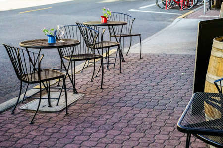 dining table and chairs: Coffeehouse provides wrought iron table and chairs for outdoor dining experience  Stock Photo
