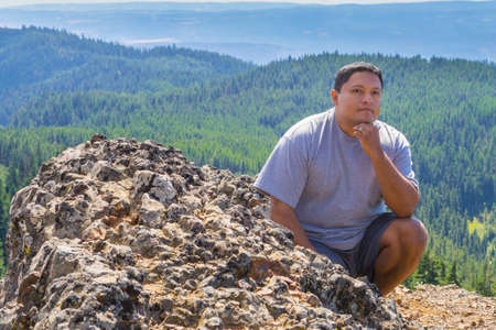 crouched: Man crouched for photo after hiking to the top of fire lookout trail Stock Photo