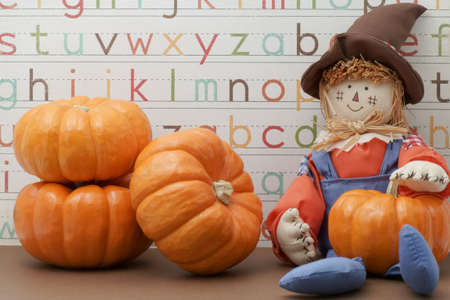 Smiling scarecrow sitting against Alphabet background holding pumpkin photo
