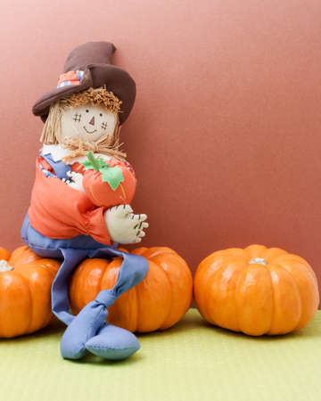 Happy scarecrow sits on pumpkins photo