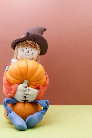 Smiling Scarecrow Holds A Pumpkin While Sitting Down photo