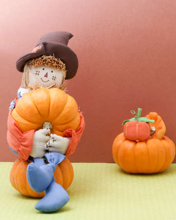 joyfully: Holiday scarecrow joyfully cradles a pumpkin