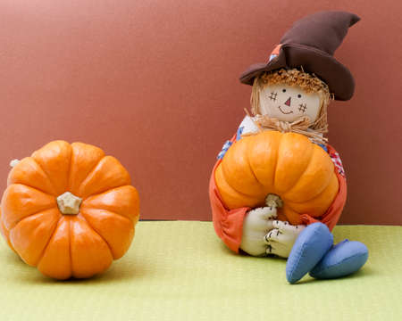 Scarecrow rag doll holds a pumpkin photo