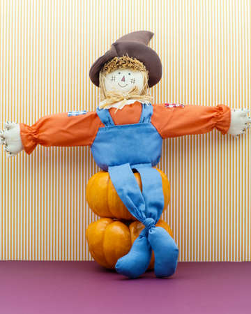 Not so scary scarecrow sits down on stacked pumpkins photo