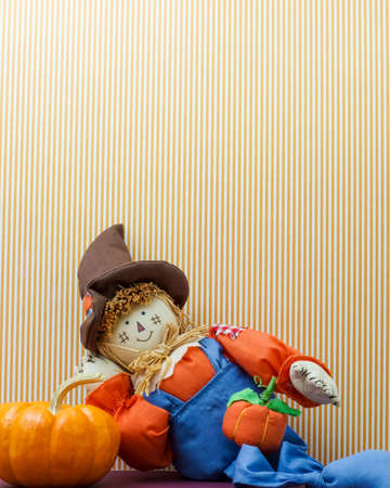 Silly happy scarecrow leans against a pumpkin photo