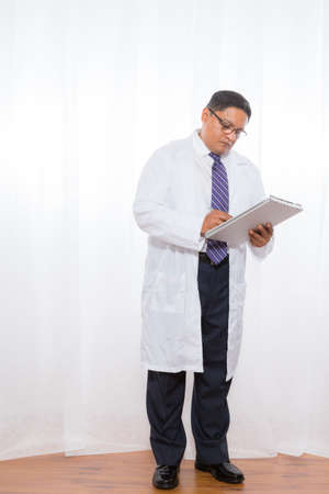 Middle aged Latino male wearing a lab coat and holding clipboard