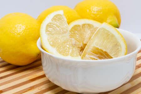 quartered: One quartered lemon inside a white bowl resting on bamboo cutting board