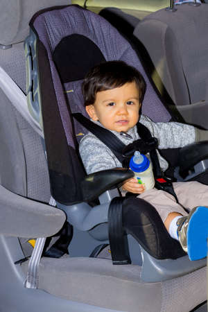 buckled: Young Handsome Male Toddler In Car Seat