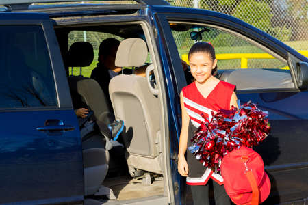 errands: Hispanic Dad Picks Up Daughter From Cheerleader Practice Stock Photo