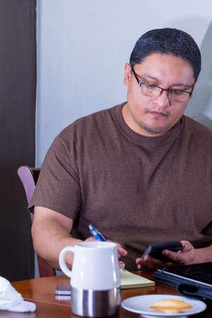 Hispanic Middle Age Male Using Calculator At Dining Table Фото со стока