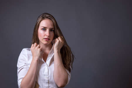 rolled up sleeves: Young woman wearing white shirt holding collar up.