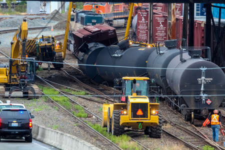 proposed: Seattle USA  July 24 2014: Workers mobilze to repair train tracks after several oil tank cars and one box car derailed underneath the Magnolia Bridge.