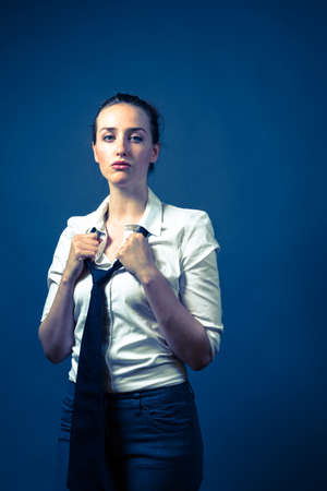 brown hair blue eyes: American female wearing a whtie button up shirt with a black tie