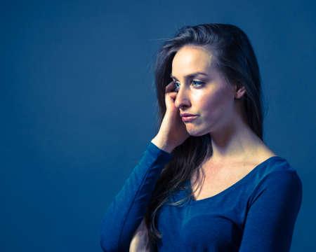 somber: Slender caucasian female with somber or gloomy expression