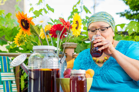 Hispanic woman enjoys an evening snack and drink on outside deck