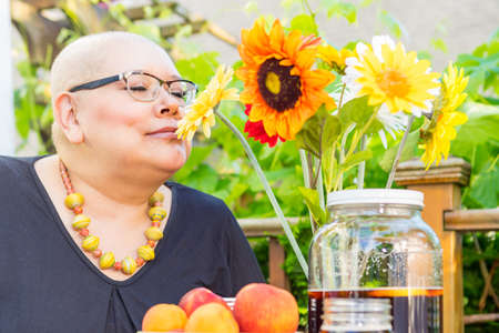 radiation therapy: Cancer patient smells scented fresh cut flowers