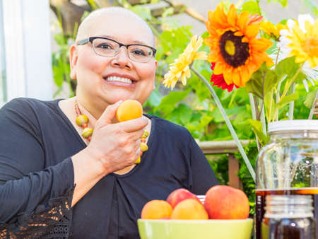 radiation therapy: Cancer patient treats herself to fresh fruit enjoying an evening outside on deck Stock Photo